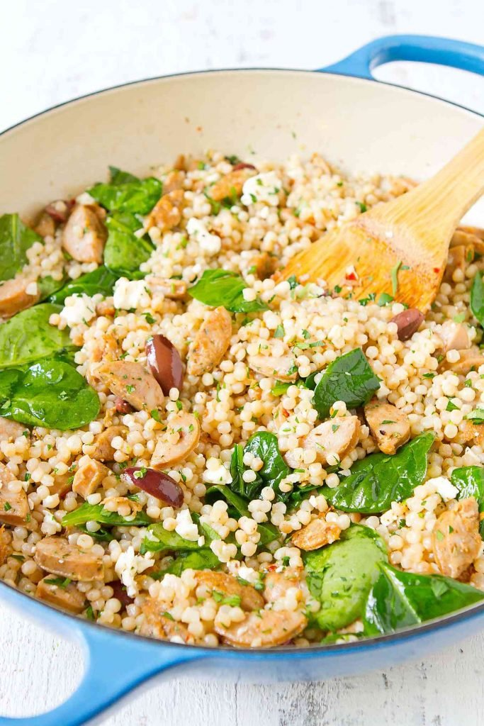 Pearl couscous, spinach, sausage, feta in a large blue skillet with wooden spatula.