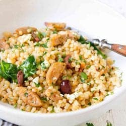 Israeli couscous, cooked sausage, spinach, olives and feta in a white bowl.