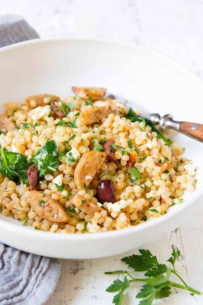 This Israeli couscous recipe is inspired by my family's favorite white wine pasta. In this recipe, chicken sausage and feta cheese add fantastic flavor to the easy sauce. | Pearl couscous | Recipes dinners | Recipes easy #israelicouscous #pearlcouscous #pastarecipes
