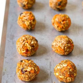No-bake energy bites filled with shredded carrots and raisins, lined up on baking sheet.