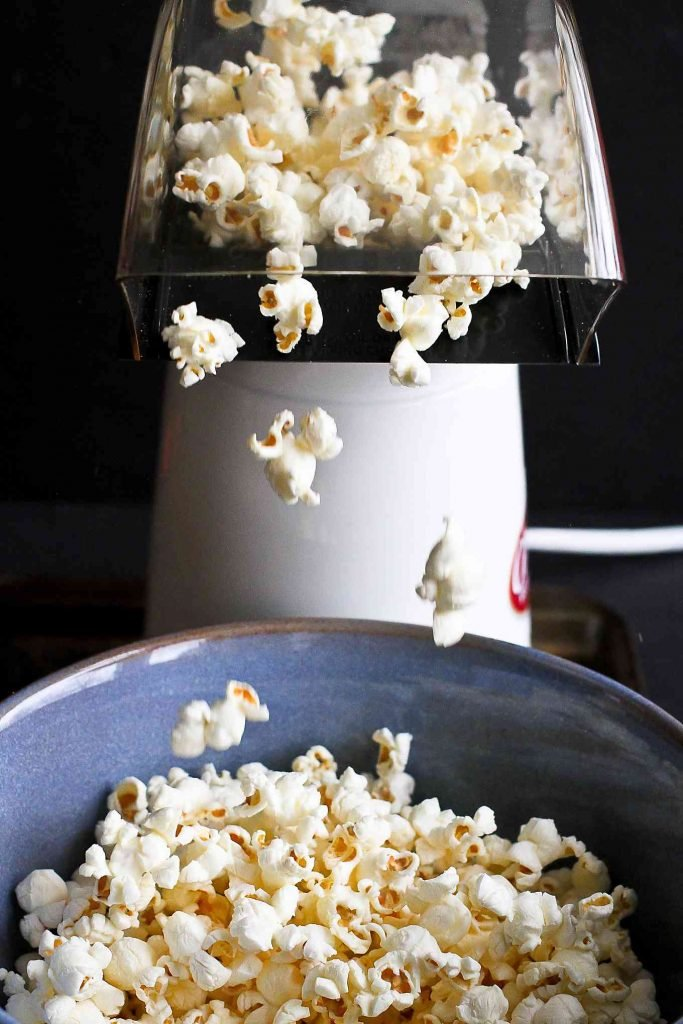 Popcorn coming out of an air popper and falling into a blue bowl
