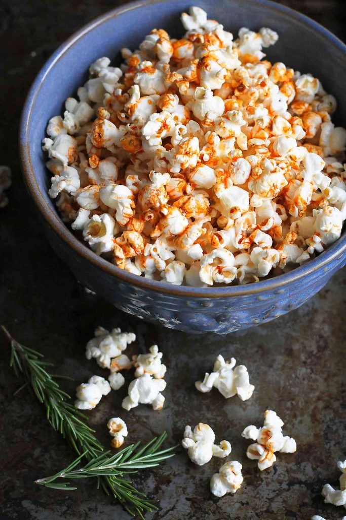 Popcorn in a large blue bowl. Topped with an olive oil, smoked paprika and rosemary mixture.