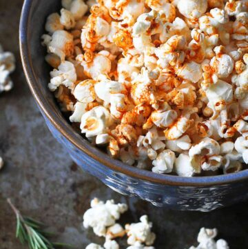 Popcorn topped with paprika olive oil, in a large blue bowl.