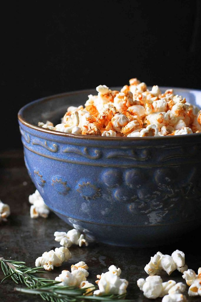 Popcorn topped with olive oil, smoked paprika and rosemary in a large blue bowl.