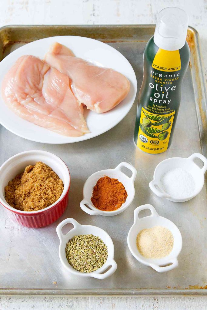 Raw chicken; spices, herbs and brown sugar in bowls; and olive oil spray on baking sheet