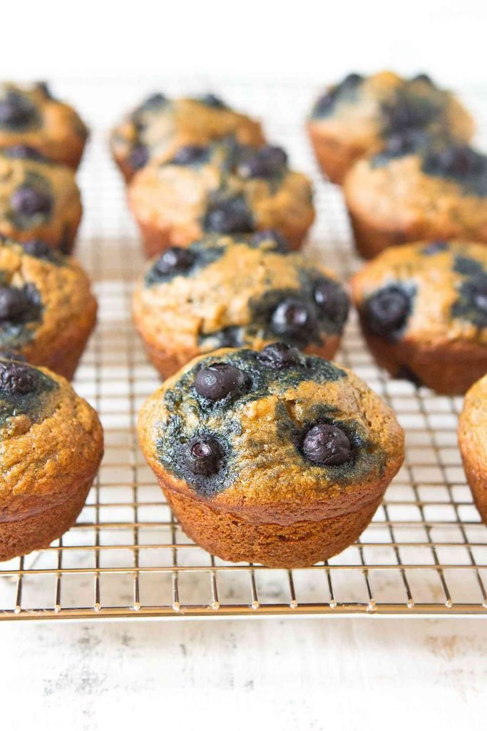 Banana and blueberry muffins cooling on a wire rack.