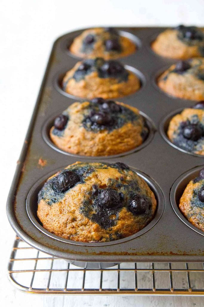 Blueberry banana muffins in a muffin tin on a wire rack.