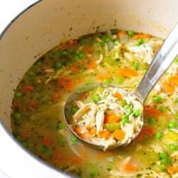 Ladle scooping chicken vegetable soup out of white saucepan.