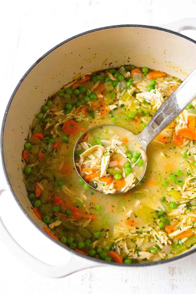 Overhead photo of silver ladle scooping out chicken soup with vegetables.