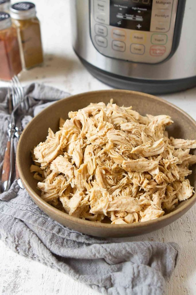 Shredded chicken in brown bowl, plus pressure cooker in the background.