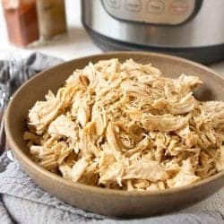 Shredded chicken in a brown bowl, with Instant Pot in background.