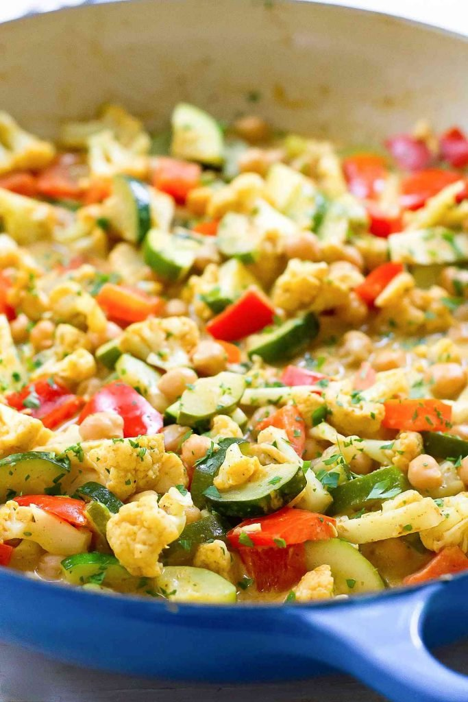 Chopped zucchini, cauliflower and bell pepper in a large blue skillet with chickpeas.