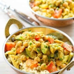 Cauliflower, zucchini and chickpea curry with quinoa in brass bowls with handles.