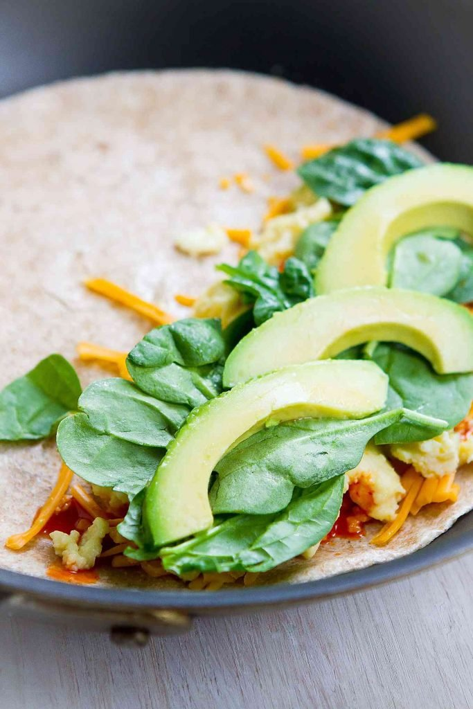 Avocado, spinach, eggs and cheese on a tortilla, in a skillet.
