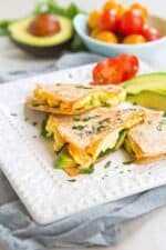 Quesadilla, but in wedges, filled with egg, avocado and spinach on a white plate.
