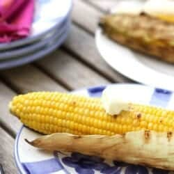 Grilled corn cobs on white and blue plates.