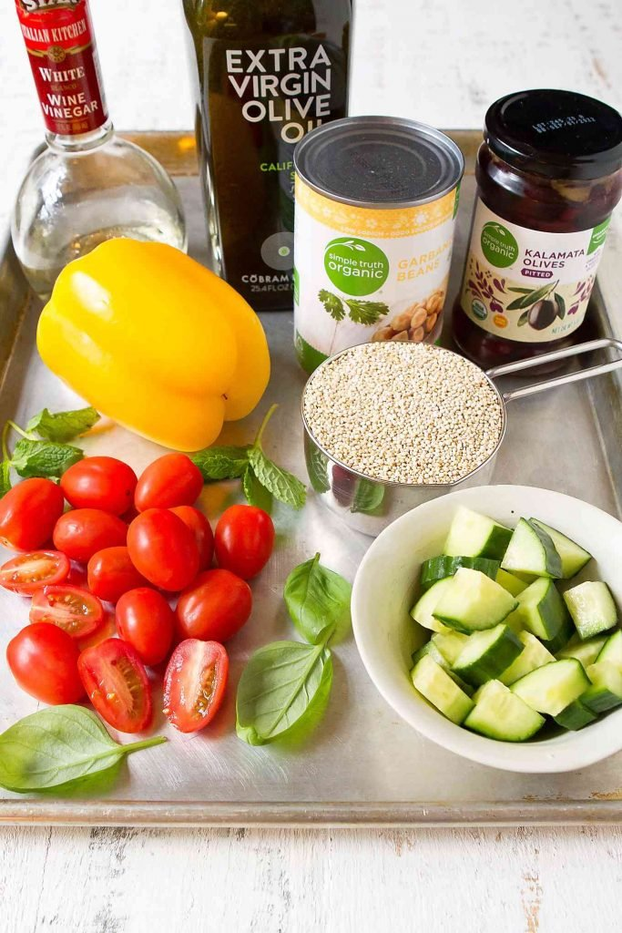 Quinoa, tomatoes, cucumber, can of chickpeas, bell pepper, olives and olive oil on a baking sheet.