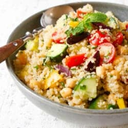 Quinoa salad with tomato, cucumber, bell pepper, herbs and olives in a gray bowl.