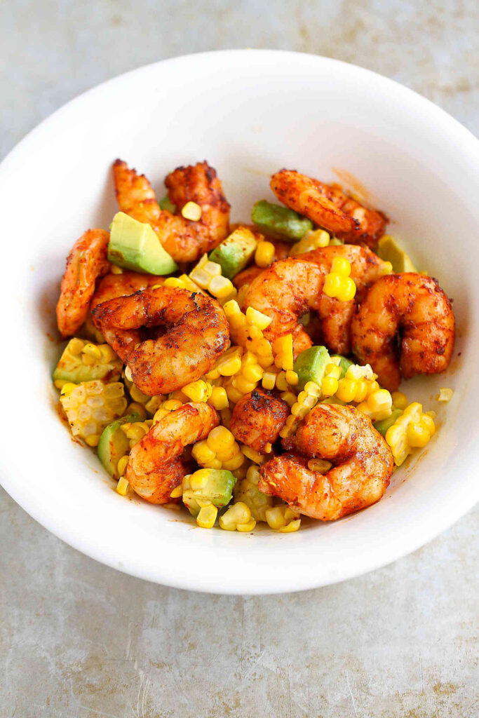 Cooked spice-encrusted shrimp, avocado and corn kernels in a white bowl.