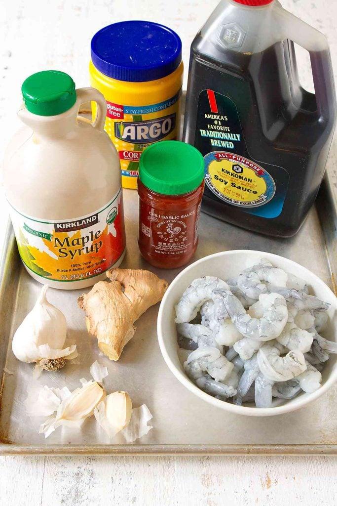 Shrimp, maple syrup, soy sauce, ginger, garlic and chili garlic sauce on a baking sheet.