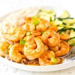 Sweet chili shrimp and green onions with rice and zucchini on a white plate.