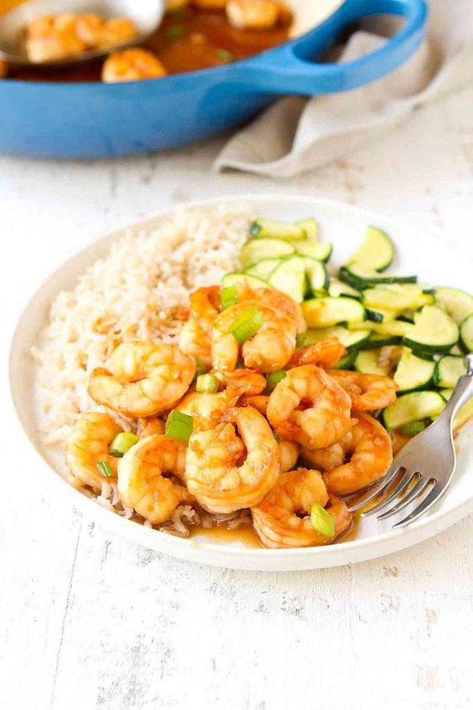 Shrimp in sweet chili sauce with rice and zucchini on plate. Skillet in background.