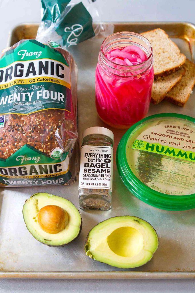 Loaf of bread, avocado, hummus, pickled onions & seasoning blend on baking sheet.
