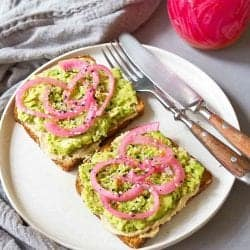 Two pieces of avocado toast topped with red onions on a white plate.