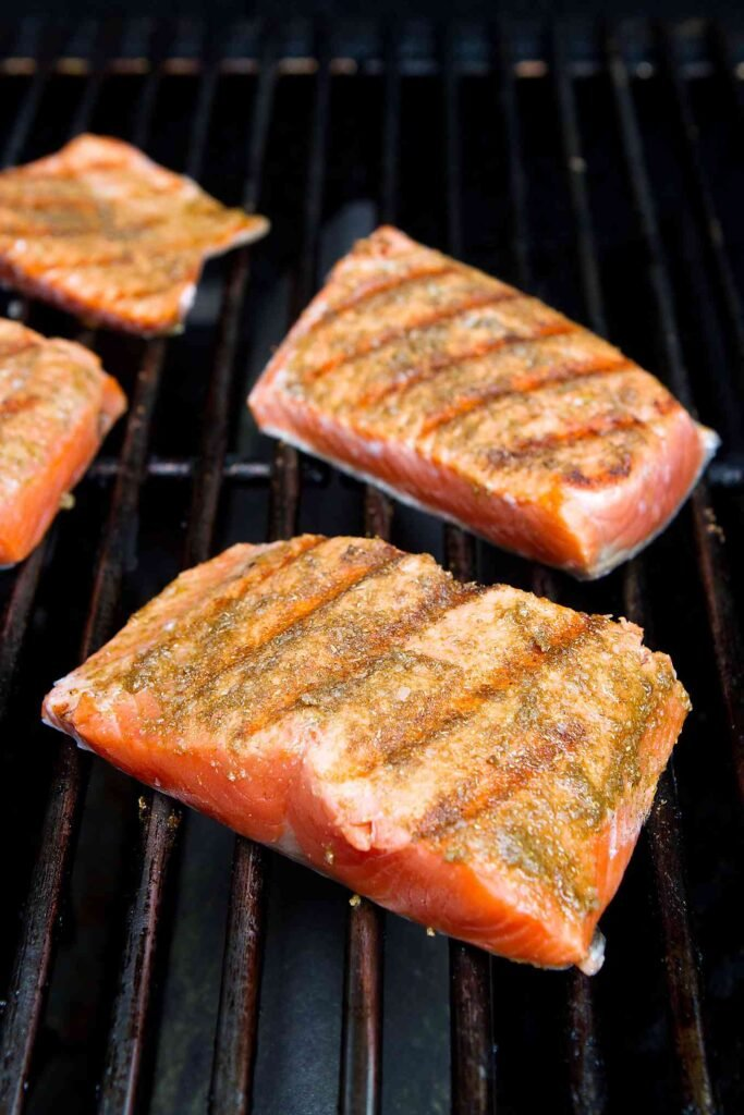 Salmon fillets on the grill, partially cooked.