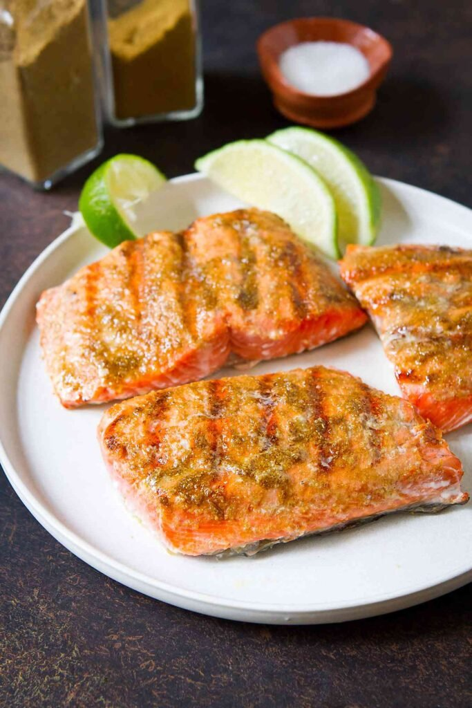 Three grilled salmon fillets on a white plate with lime wedges.