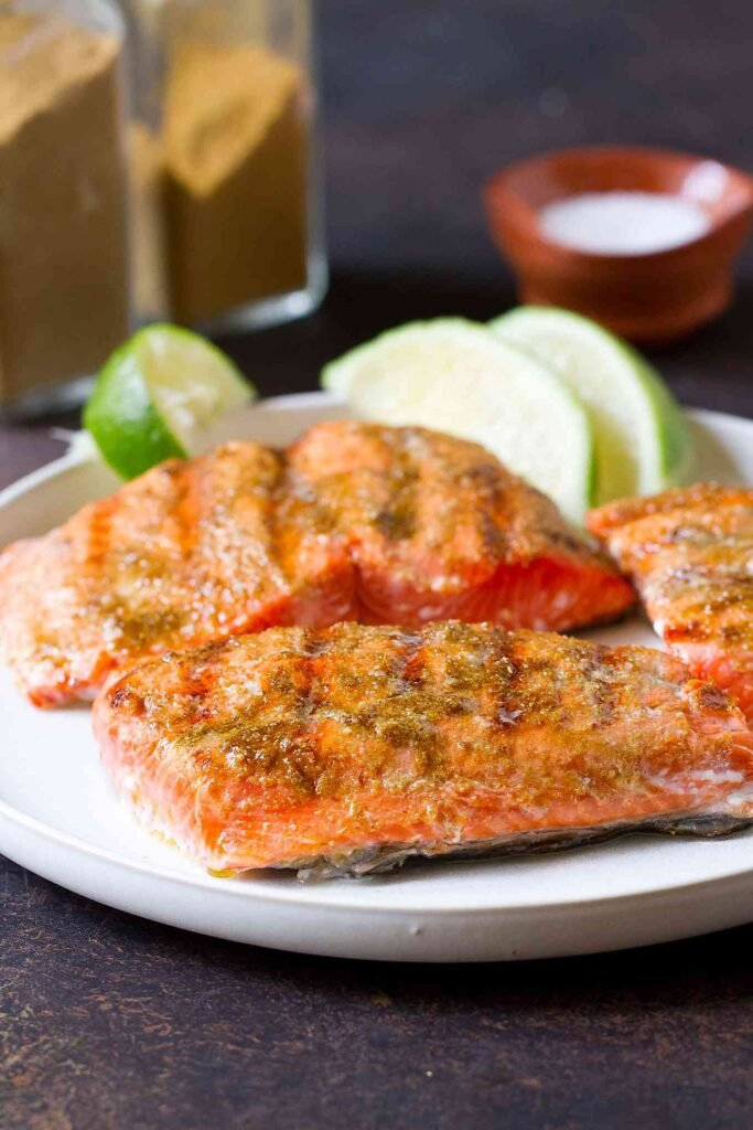 Cooked salmon fillets and limes on a white plate, with spice bottles behind.
