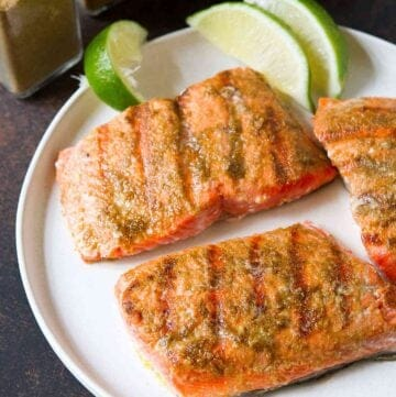 Pieces of grilled salmon and lime wedges on a white plate.