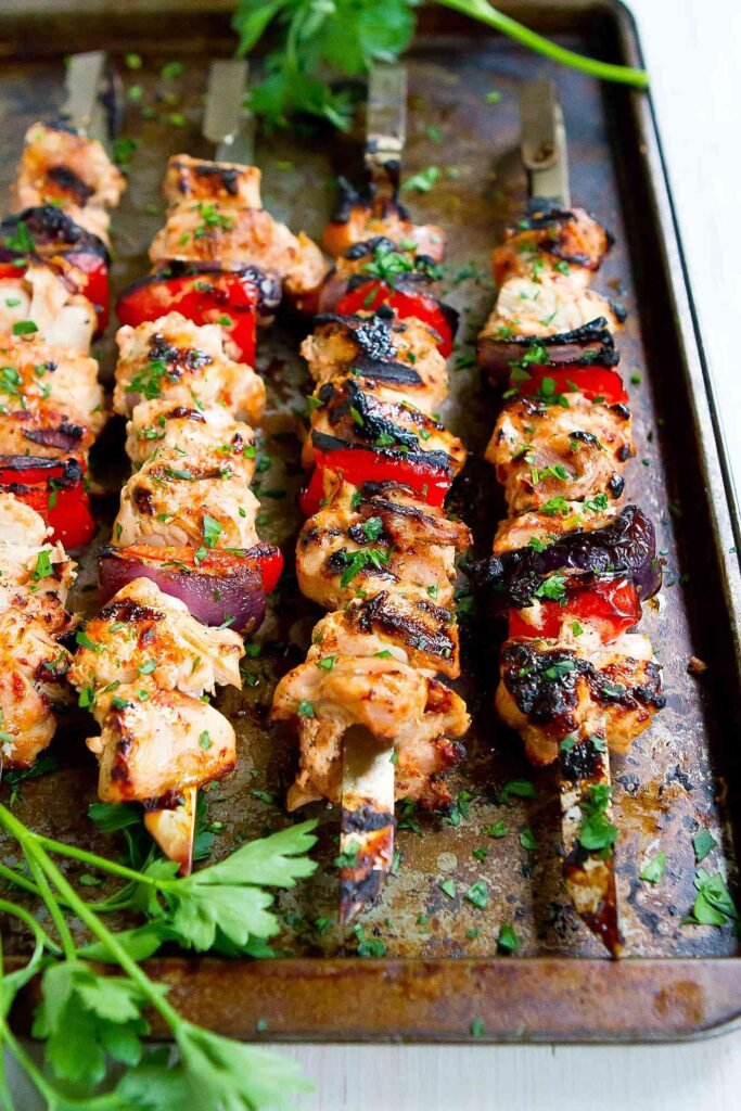 Grilled smoked paprika chicken, alternating with grilled red bell pepper and onion, on skewers.