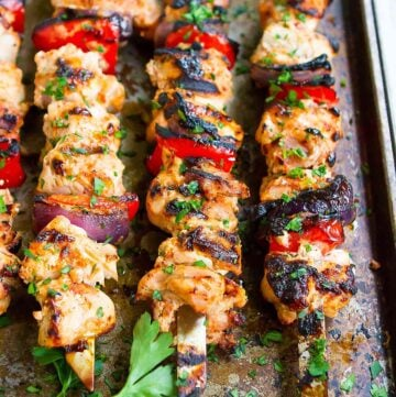 Chicken kabobs with bell peppers and onions, resting on a baking sheet.