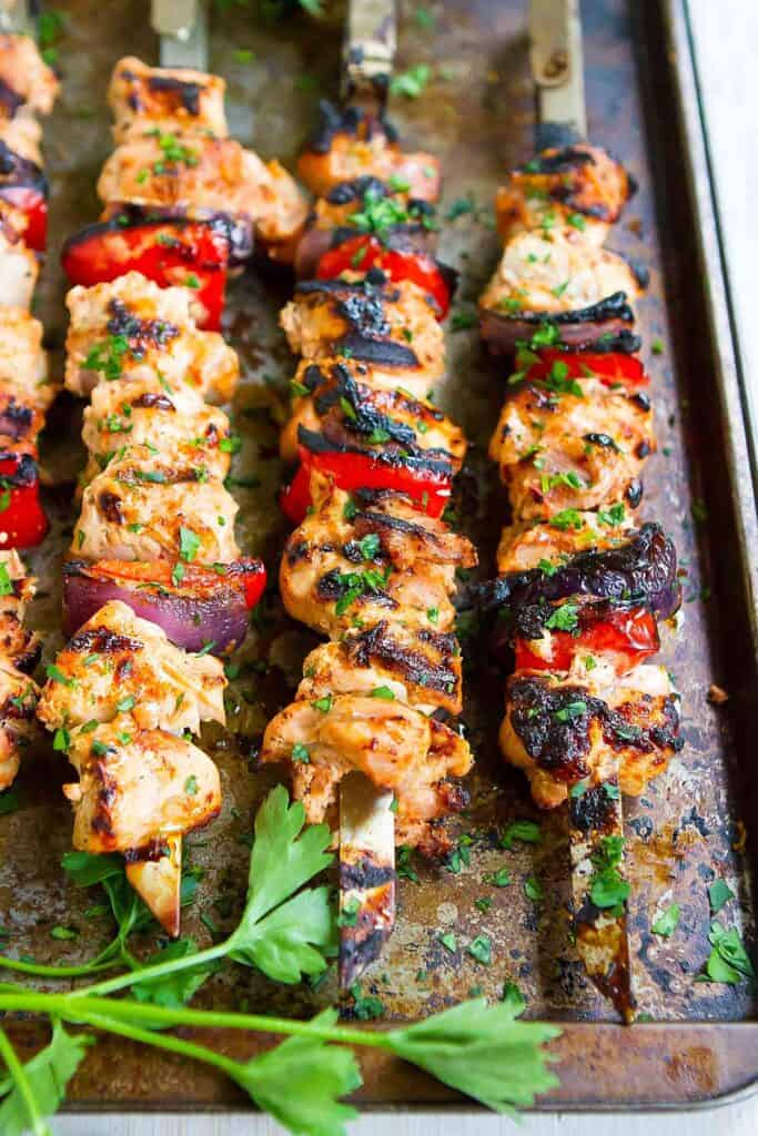 Smoked paprika chicken kabobs with bell peppers and onions, resting on a baking sheet.