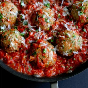 Baked turkey meatballs in a tomato sauce, all in a large skillet.