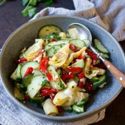 Cucumber, roasted red peppers and artichokes in a gray bowl, with parsley in background.