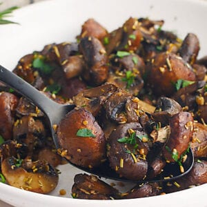 Roasted mushrooms with garlic and rosemary in a white bowl.