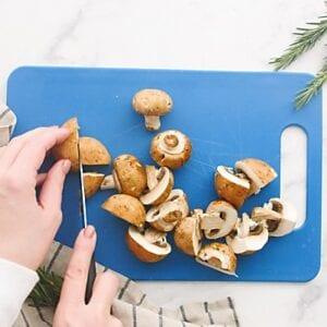 Cutting mushrooms into halves on a blue cutting board.