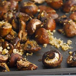 Roasted mushrooms and garlic on a baking sheet.