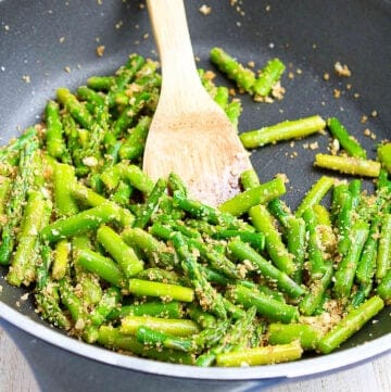 Sauteed asparagus, mixed with garlicky breadcrumbs, in a black skillet.