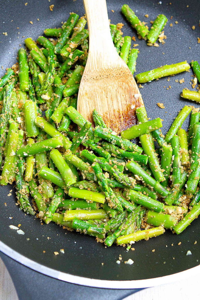 Pieces of sauteed asparagus with garlic breadcrumbs in a large nonstick skillet.