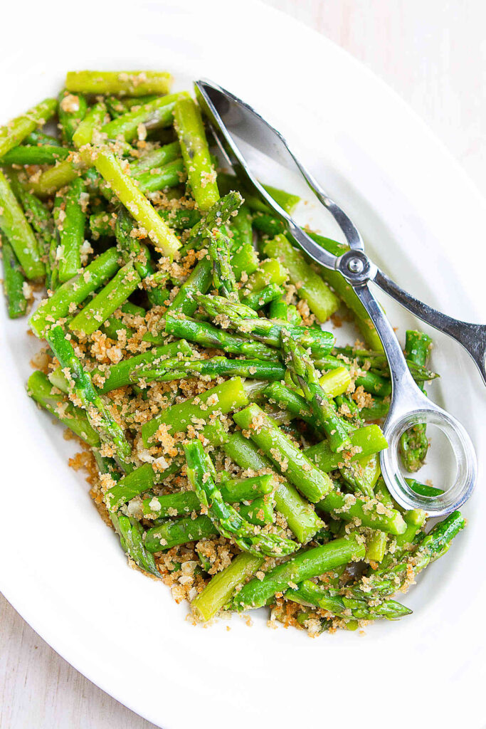 Cut and sauteed asparagus and panko breadcrumbs on a white plate.