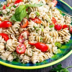 Tuna pasta salad with grape tomatoes in a blue-green bowl.