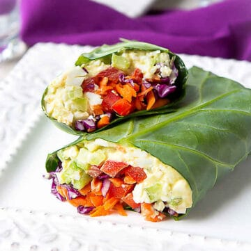 Collard green wraps filled with egg salad and vegetables, on a white plate.