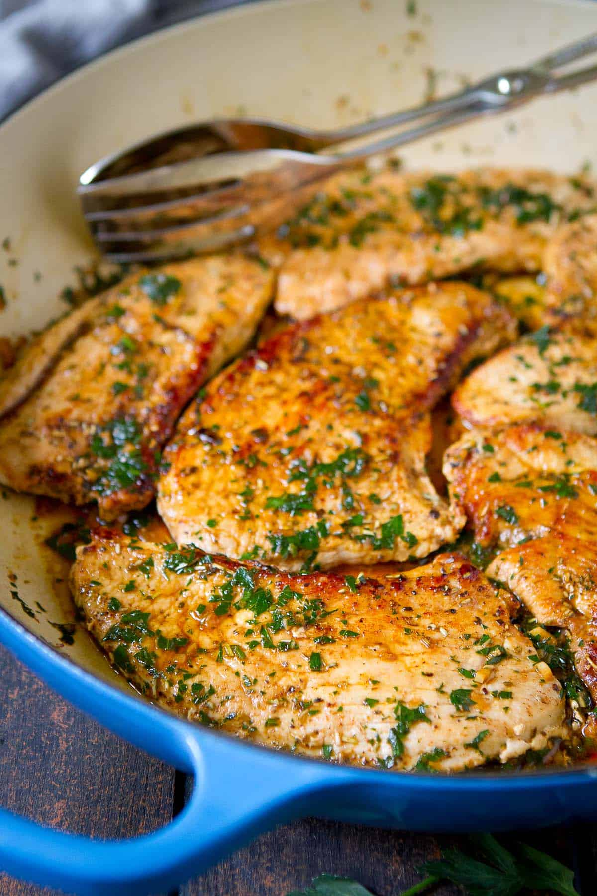 Cooked turkey cutlets with white wine sauce in a skillet.
