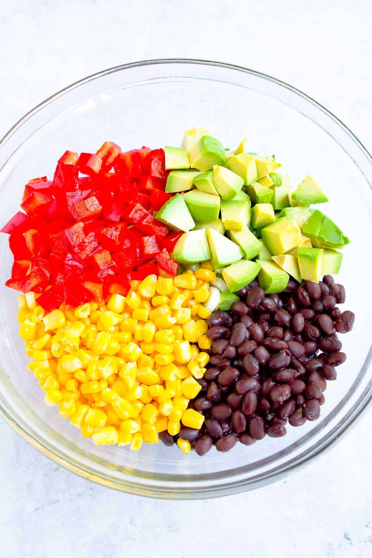 Black beans, corn, avocado and red bell pepper in a glass bowl.