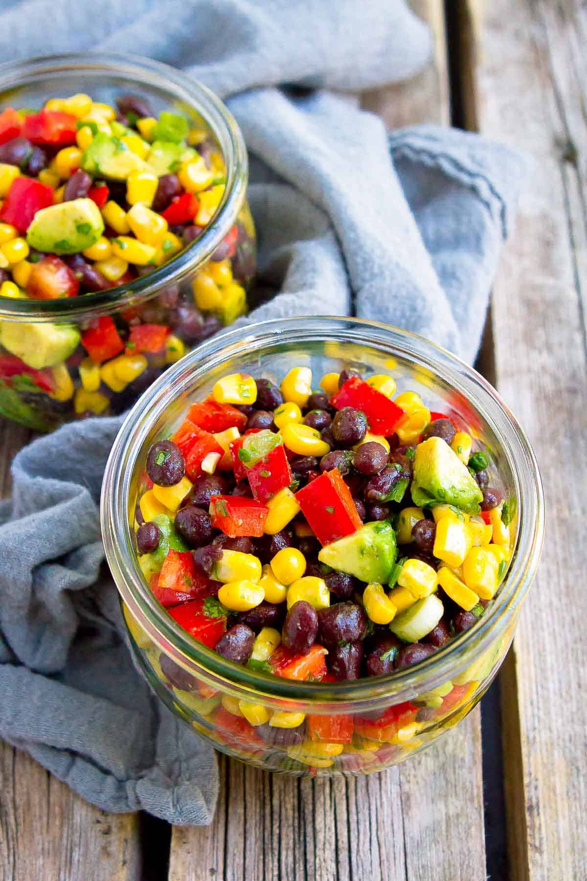 Corn, beans, peppers and avocado in canning jars, with gray napkin.