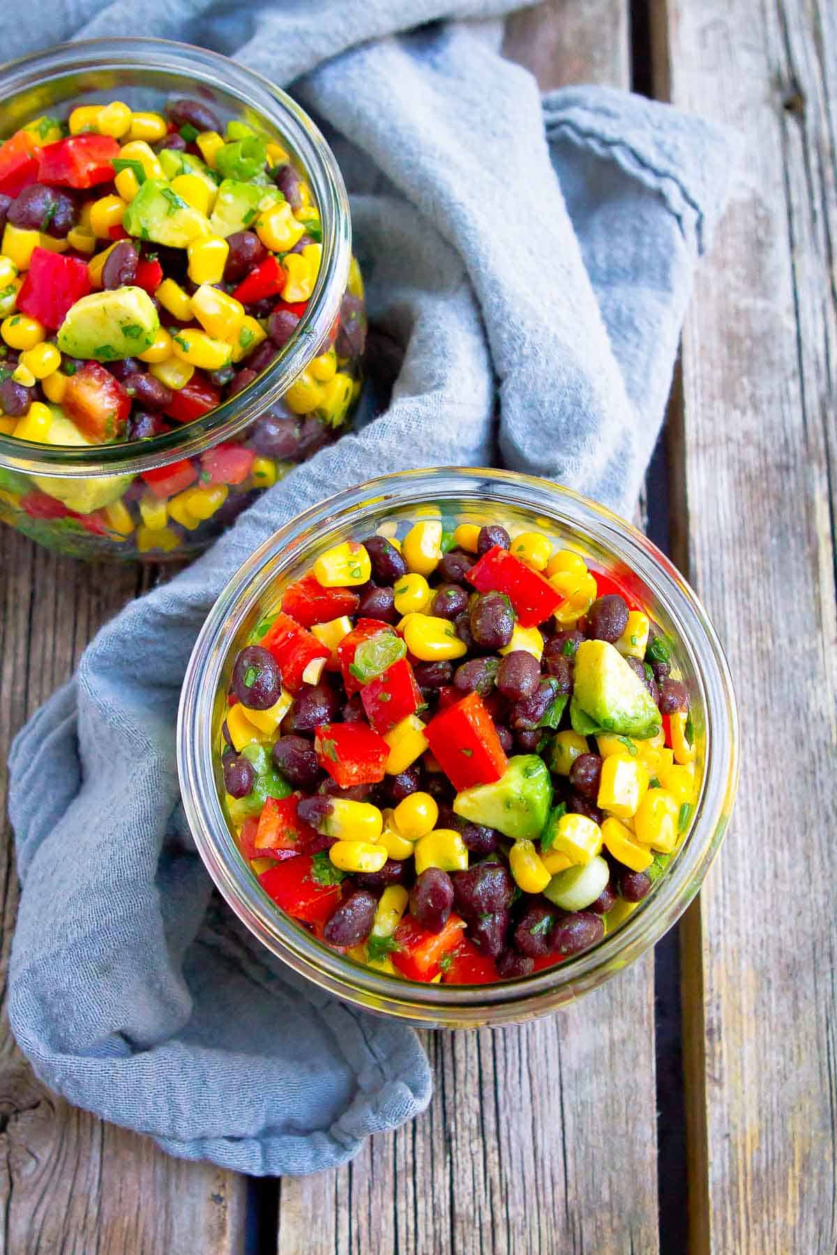 Overhead photo of corn bean salad in glass jars on wooden table.