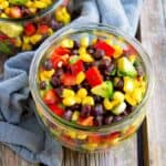 Black bean and corn salad with avocado in a glass jar.